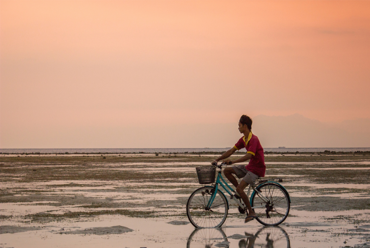 Indonesian man on bike. Photo by Luca Zanon